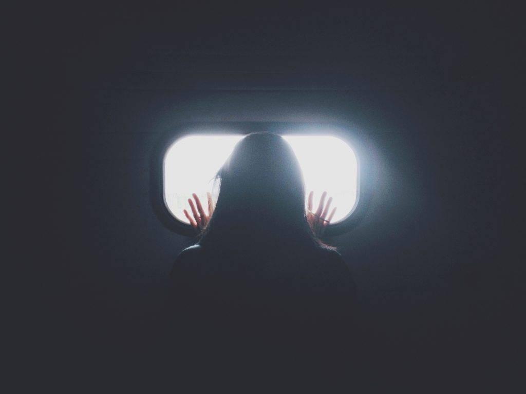 niña clarividente mirando fuera de una ventana