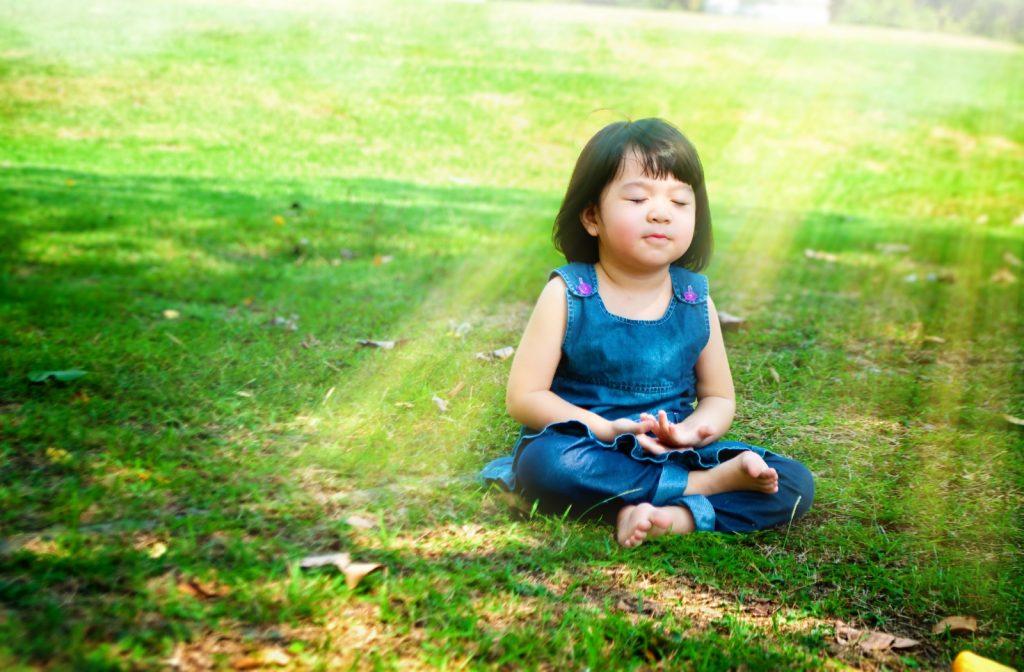 niña en un parque meditando