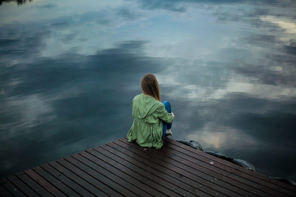 Mujer triste en un lago. El secreto de la curación.