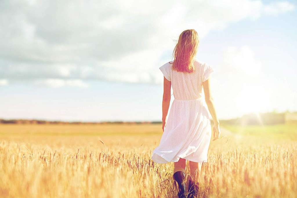 Mujer andando por un campo de trigo.