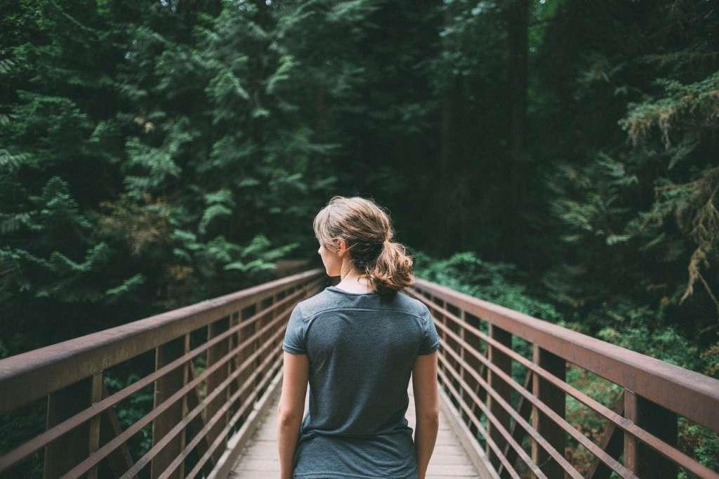 Chica en un puente de un bosque realizando la meditación caminando