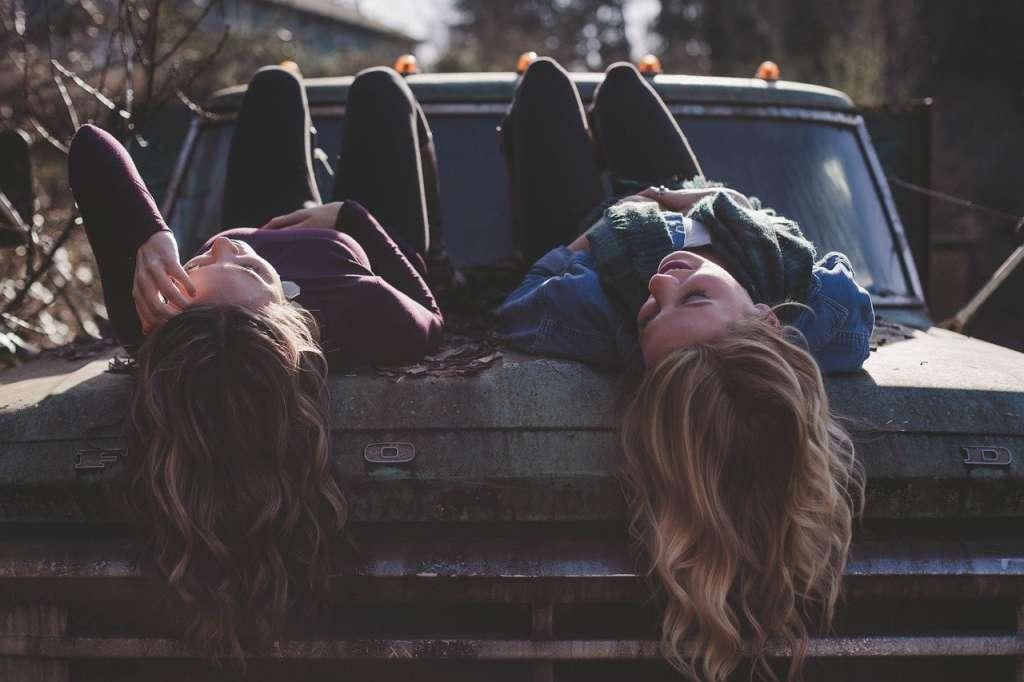 Dos chicas encima de un coche abandonado en como ser uno mismo