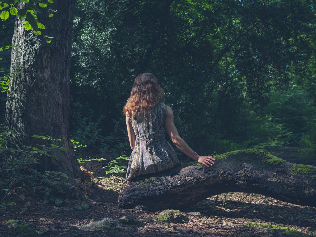 Una mujer sentada y practicando la inmersión en la madre naturaleza