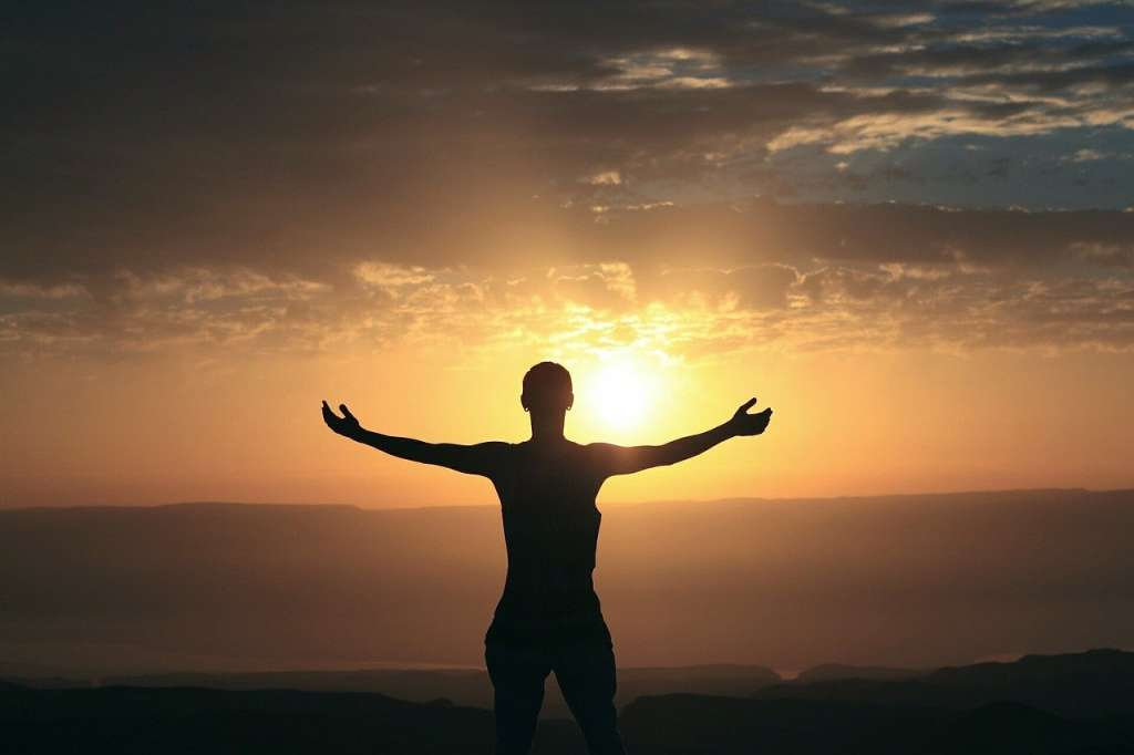 Mujer saludando al sol.