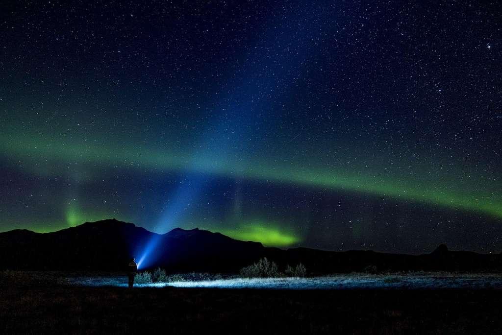 Una persona con una linterna iluminando el cielo por la noche y siguiendo las señales de la vida