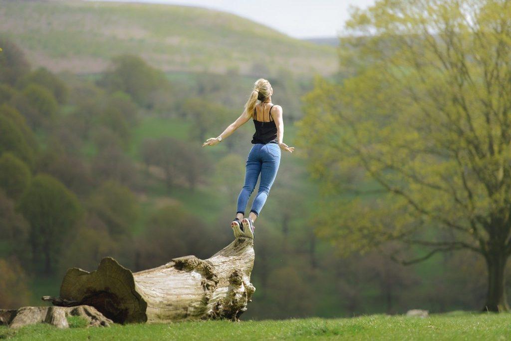 Mujer saltando desde un árbol