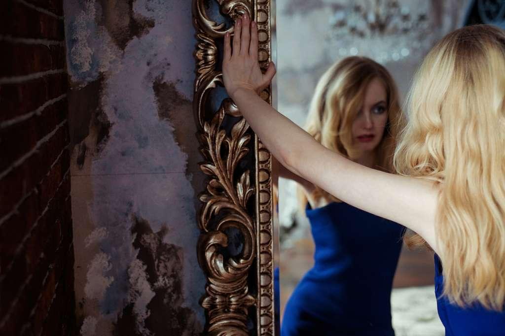 Mujer mirandose en un espejo y realizando el trabajo espejo